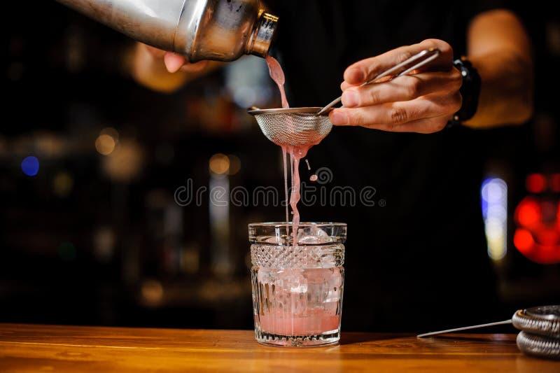 Mano del camarero que vierte la bebida rosada del cóctel en barra imagenes de archivo