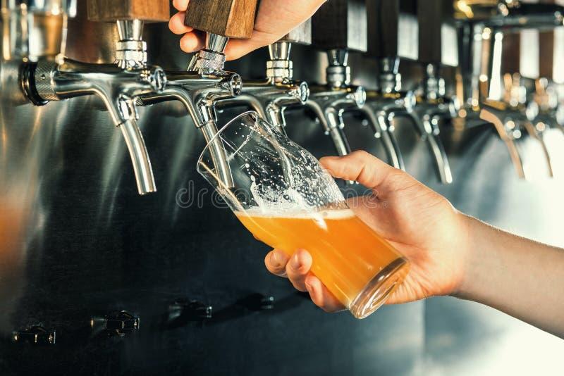 Mano del camarero que vierte una cerveza de cerveza dorada grande en golpecito imágenes de archivo libres de regalías
