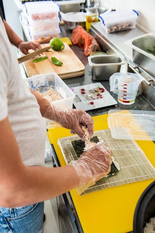 Mano del cocinero que hace el rollo de sushi japonés El cocinero japonés en el trabajo prepara el rollo de sushi delicioso con el fotografía de archivo libre de regalías