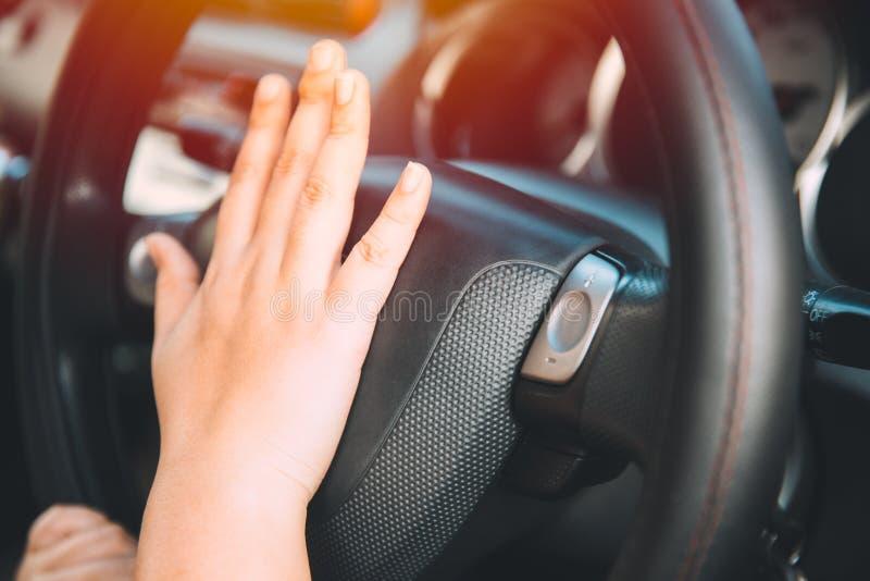 Mano del conductor de las mujeres del primer en el cuerno del volante foto de archivo
