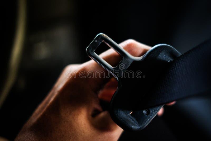 Mano del conductor que sostiene la cerradura del cinturón de seguridad del cinturón de seguridad en coche imágenes de archivo libres de regalías