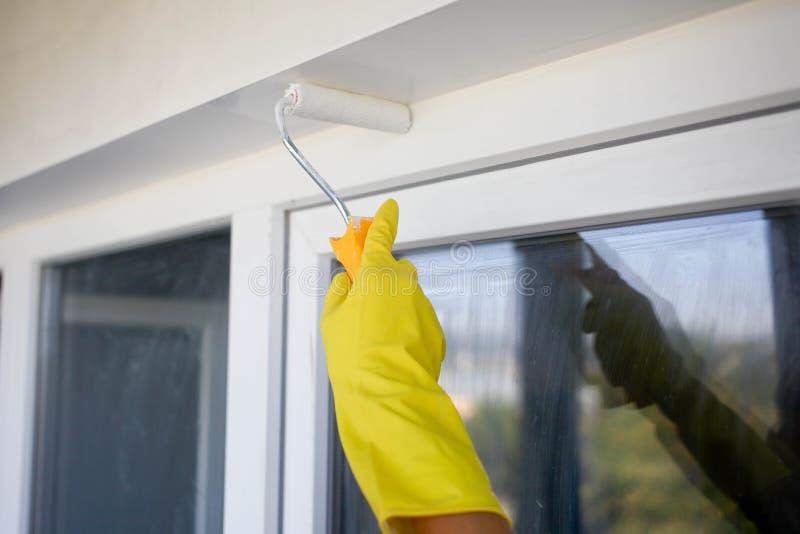 mano del constructor en el guante amarillo que pinta una pared con el rodillo de pintura fotos de archivo