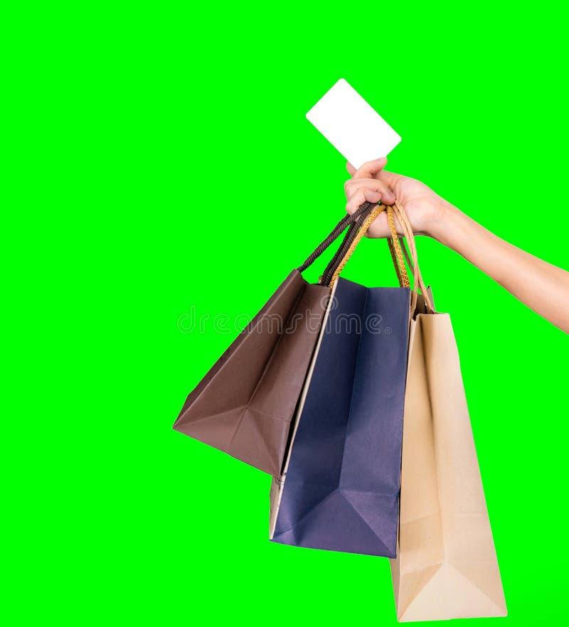 Mano del consumatore di donna che tengono sacchetto della spesa variopinto e carta di credito isolata su fondo verde Concetto di  immagini stock libere da diritti