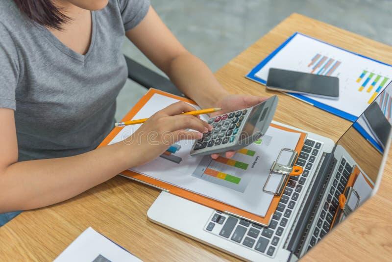 Mano del contable usando la calculadora para comprobar informes financieros foto de archivo
