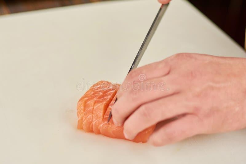 Mano del cuoco unico che affetta alto vicino del salmone fotografie stock