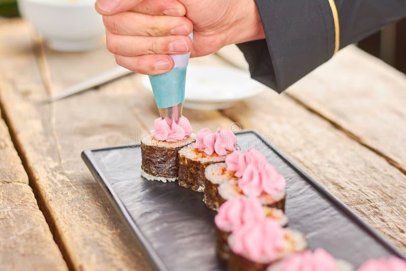 Mano del cuoco unico che decora i sushi con crema immagini stock libere da diritti