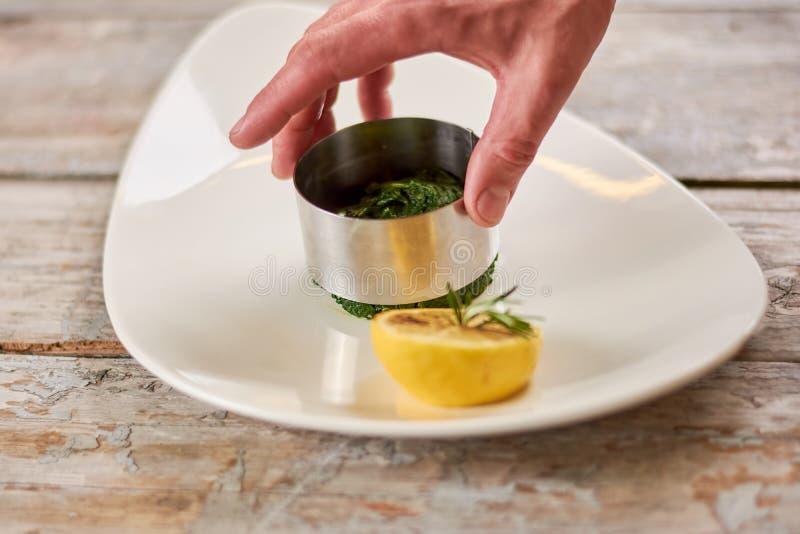 Mano del cuoco unico che forma un piatto fotografia stock