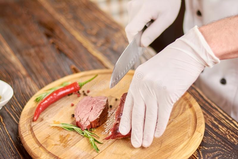 Mano del cuoco unico con la bistecca di manzo di taglio del coltello immagini stock