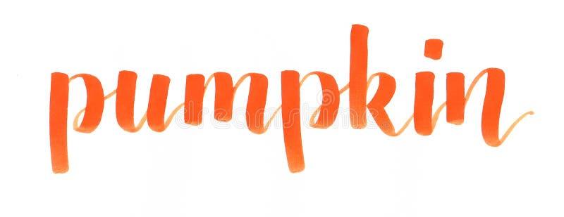 Mano del ` de la calabaza del ` que pone letras a la inscripción anaranjada en el ambiente de Halloween stock de ilustración