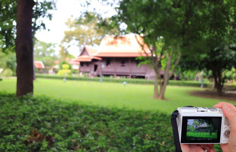 Mano del ` de la mujer que sostiene una cámara para tomar la imagen de una casa tradicional del vintage del estilo tailandés impr foto de archivo