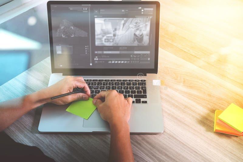 Mano del diseñador del sitio web que asiste a videoconferencia con COM del ordenador portátil imagen de archivo
