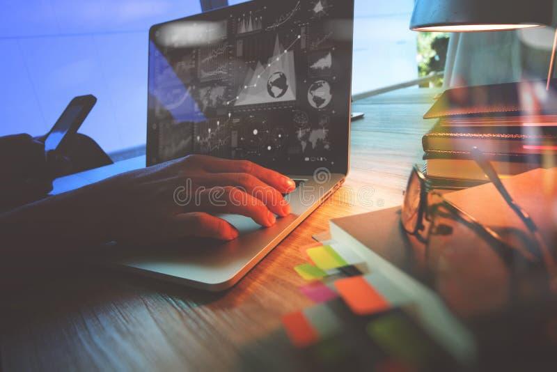 Mano del diseñador que trabaja con el ordenador portátil en el escritorio de madera como res foto de archivo libre de regalías