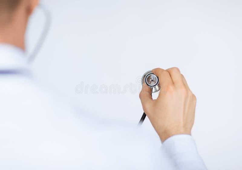 Mano del doctor con el estetoscopio que escucha alguien fotografía de archivo