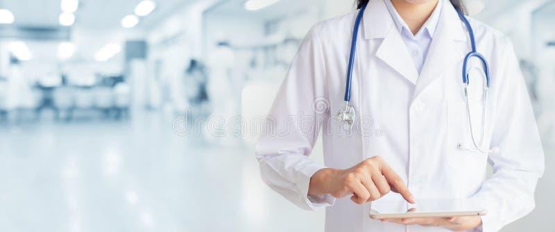 Mano del doctor que toca en la tableta en oficina del hospital imagen de archivo libre de regalías