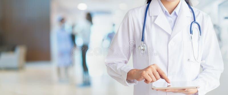 Mano del doctor que toca en la tableta en oficina del hospital fotografía de archivo