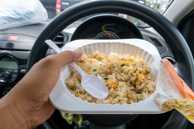 Mano del driver alla ruota mentre mangiando alimenti a rapida preparazione nel traffico immagine stock libera da diritti