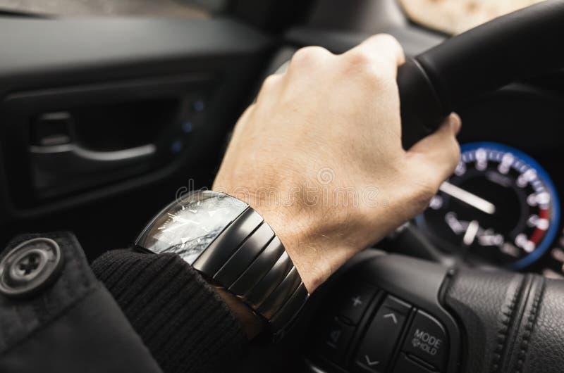 Mano del driver con l'orologio su un volante fotografia stock