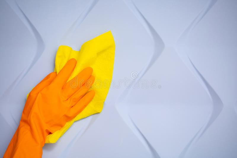 Mano del empleado en el guante protector de goma anaranjado que limpia la pared azul 3d del polvo con el trapo seco amarillo Limp imagenes de archivo