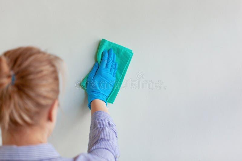 Mano del empleado en el guante protector de goma azul que limpia la pared del polvo con el trapo seco Compañía de limpieza comerc fotos de archivo