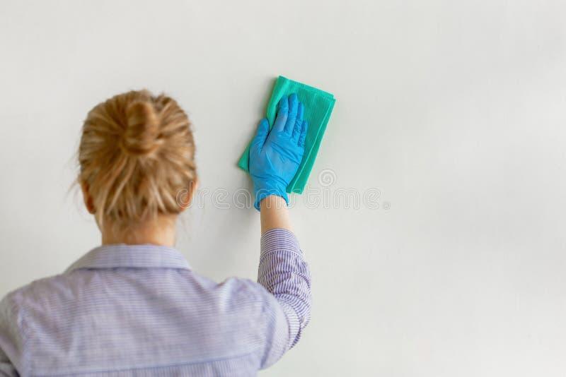 Mano del empleado en el guante protector de goma azul que limpia la pared del polvo con el trapo seco Compañía de limpieza comerc imagen de archivo