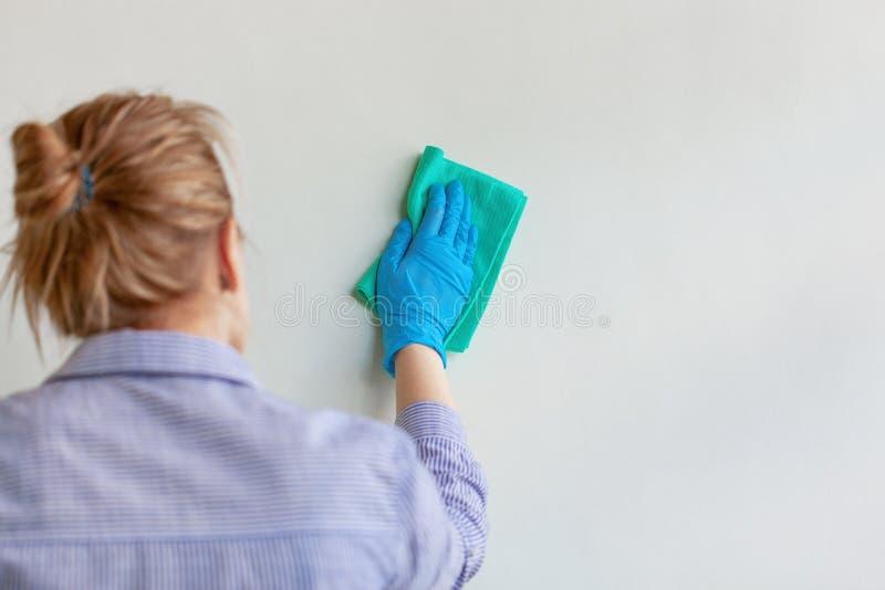 Mano del empleado en el guante protector de goma azul que limpia la pared del polvo con el trapo seco Compañía de limpieza comerc fotografía de archivo libre de regalías