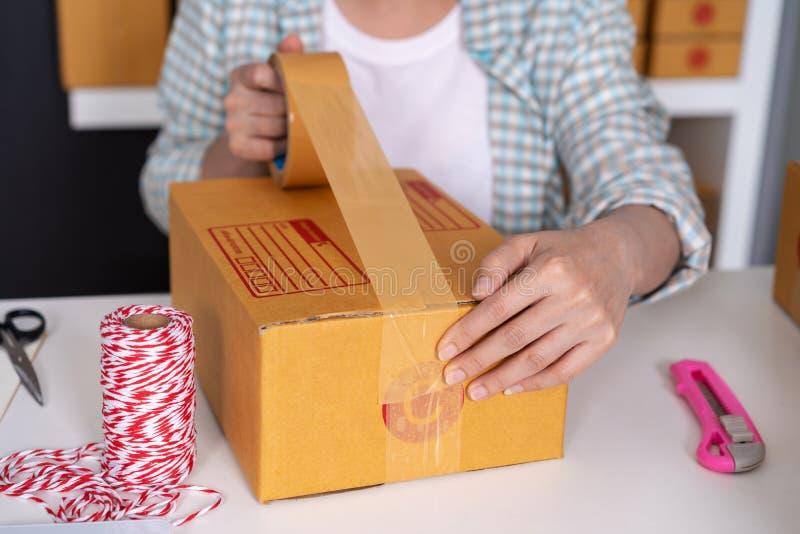 Mano del empresario en línea de la mujer que usa la cinta al paquete que embala b foto de archivo libre de regalías