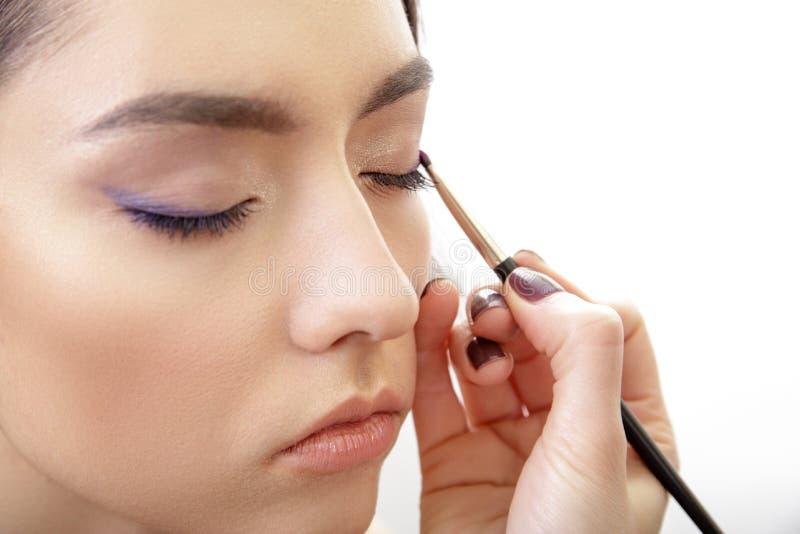 Mano del estilista que aplica maquillaje del ojo a los párpados imagen de archivo libre de regalías