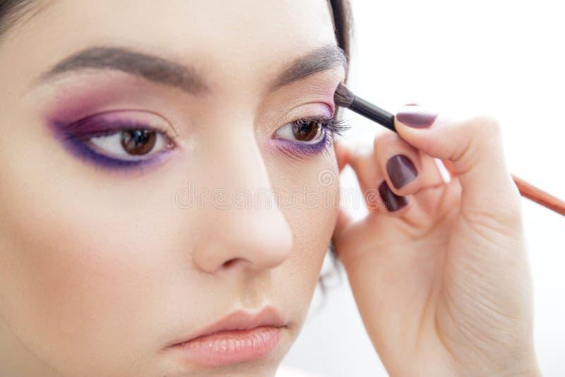 Mano del estilista que aplica maquillaje del ojo a los párpados imagen de archivo