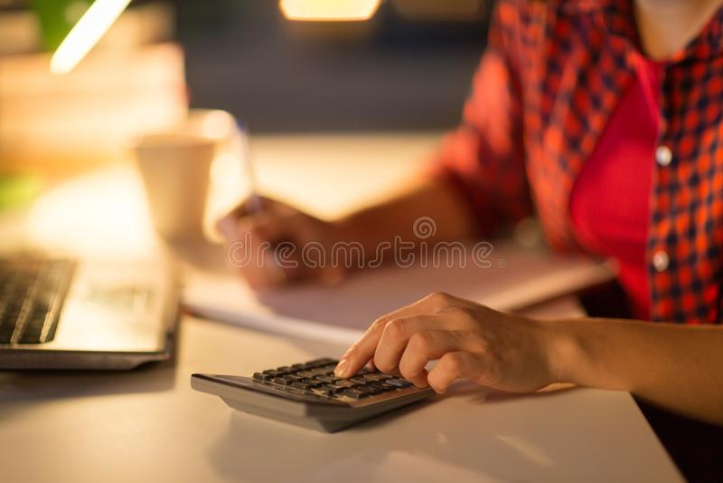 Mano del estudiante que cuenta por la calculadora en casa fotos de archivo libres de regalías