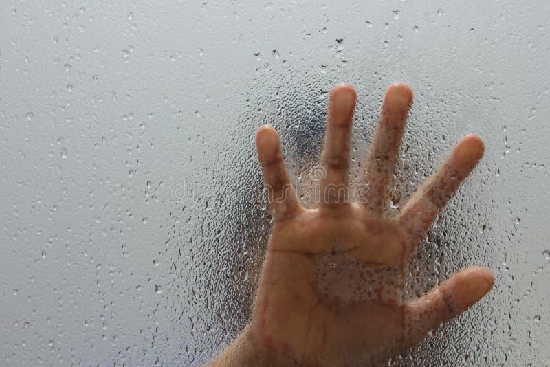 Mano del extranjero en el vidrio esmerilado con descenso del agua fotografía de archivo libre de regalías