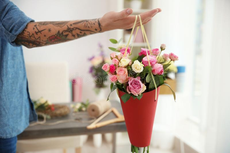 Mano del florista tatuado que sostiene el cono de papel imagenes de archivo