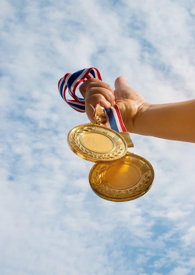 mano del ganador aumentada y que sostiene dos medallas de oro contra el cielo azul imágenes de archivo libres de regalías