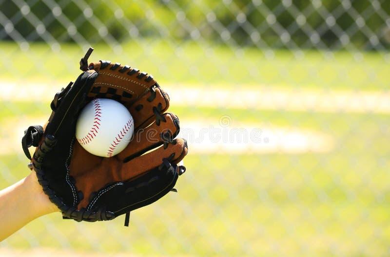 Mano del giocatore di baseball con il guanto e della palla sopra il campo fotografie stock libere da diritti