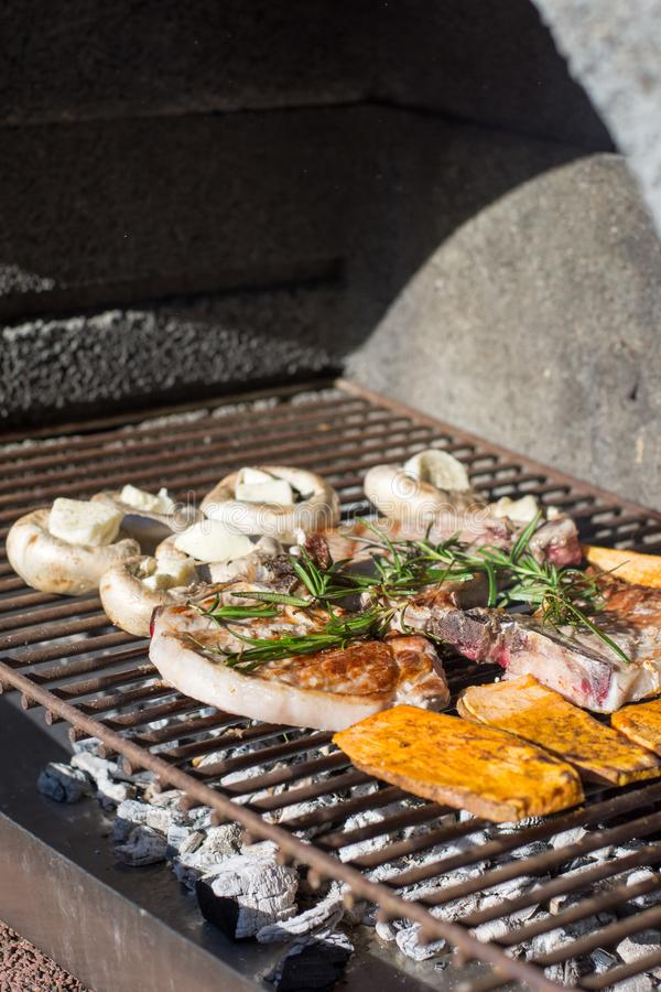 Mano del giovane che griglia una certe carne e verdura immagini stock libere da diritti