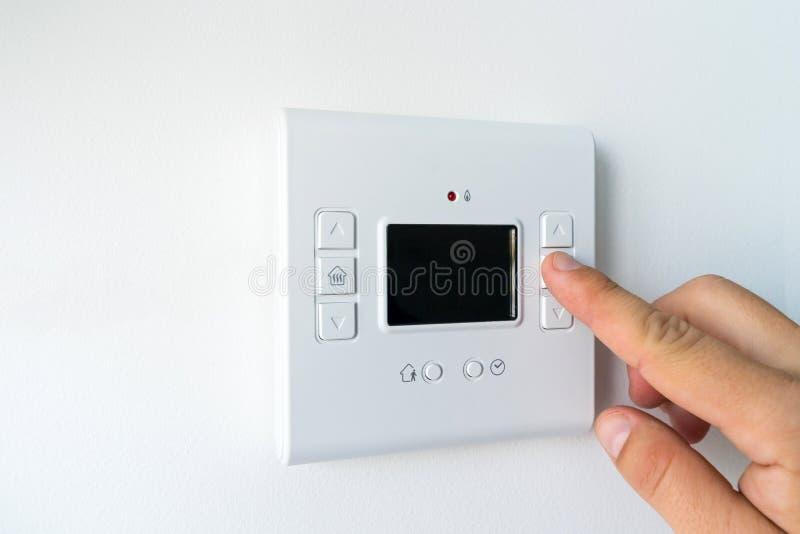 Mano del hombre ajustando la temperatura ambiente en una caldera de agua termostato programable moderna. Inicio inteligente fotos de archivo libres de regalías