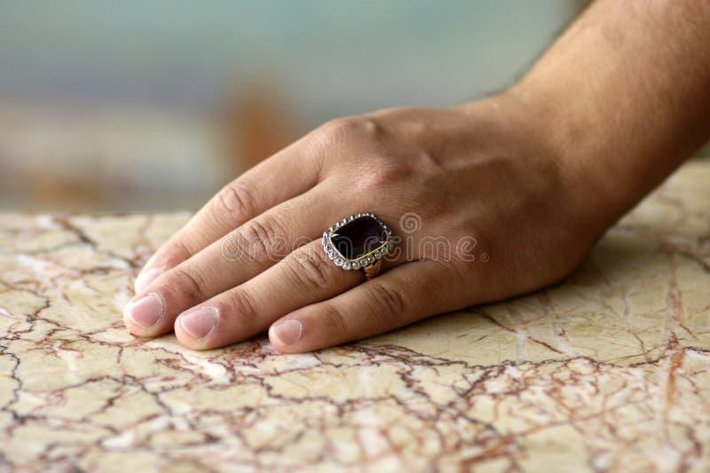 Mano del hombre con el anillo antiguo en el mármol ligero imagen de archivo libre de regalías