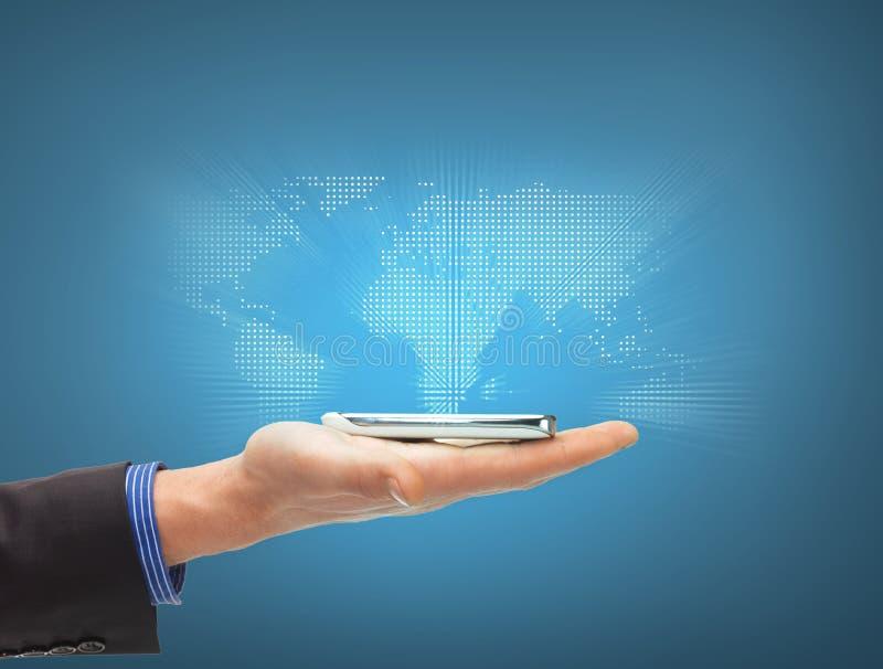 Mano del hombre con smartphone y el mapa del mundo virtual imagen de archivo libre de regalías