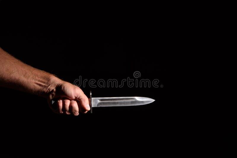Mano del hombre con un cuchillo fotos de archivo