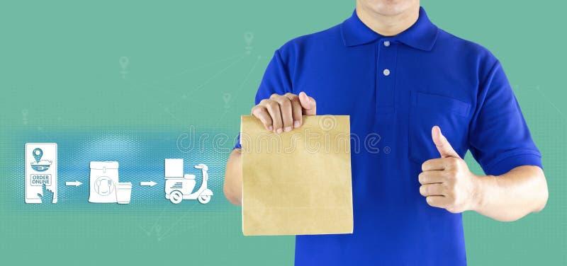 Mano del hombre de entrega que sostiene la bolsa de papel en los medios azules del uniforme y del icono para entregar servicio de imagen de archivo libre de regalías