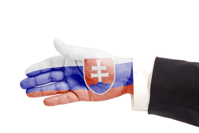 Mano del hombre de negocios del gesto del apretón de manos con la bandera de Eslovaquia foto de archivo