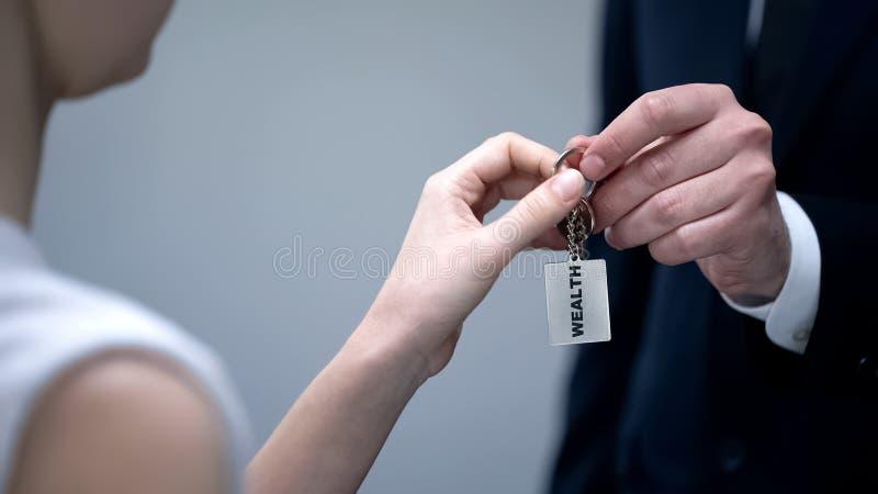 Mano del hombre de negocios que da llaves de la mujer a la riqueza, compartiendo secretos del primer del éxito imagenes de archivo