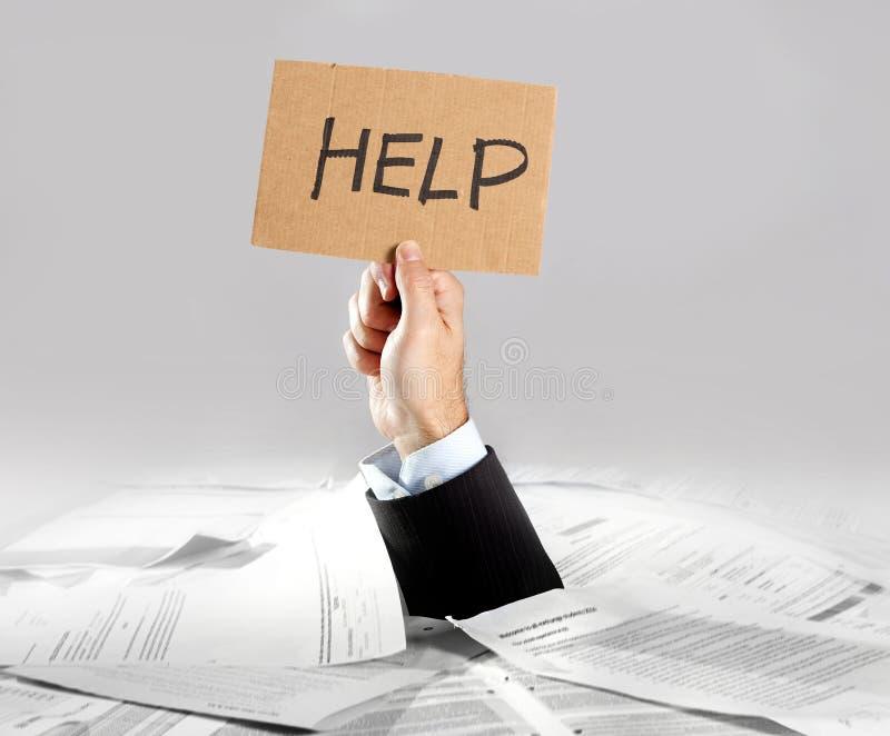Mano del hombre de negocios que emerge de mensaje cargado de la ayuda de la tenencia del escritorio del papeleo foto de archivo