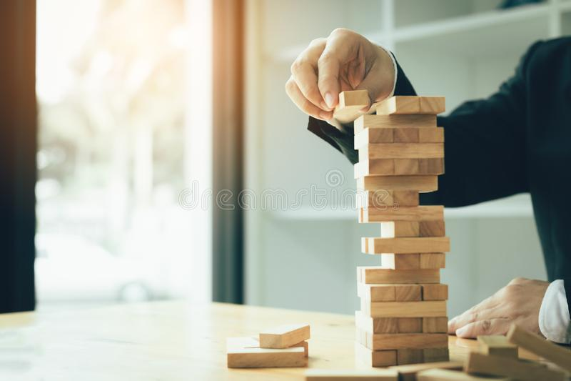 Mano del hombre de negocios que juega al juego de las pilas de los bloques de madera con la estrategia del planeamiento de la ges fotos de archivo libres de regalías