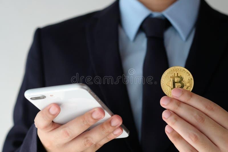 Mano del hombre de negocios que lleva a cabo el bitcoin y que usa smartphone sobre blanco fotos de archivo