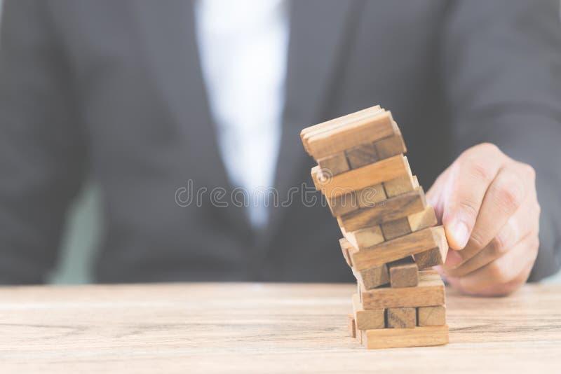 Mano del hombre de negocios que lleva a cabo el bloque de madera con la casa blanca modelo Riesgo e incertidumbre de inversi?n en imágenes de archivo libres de regalías