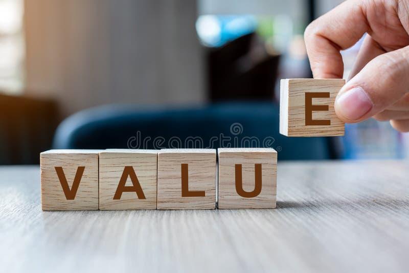 Mano del hombre de negocios que lleva a cabo el bloque de madera del cubo con palabra del negocio del valor en fondo de la tabla  foto de archivo