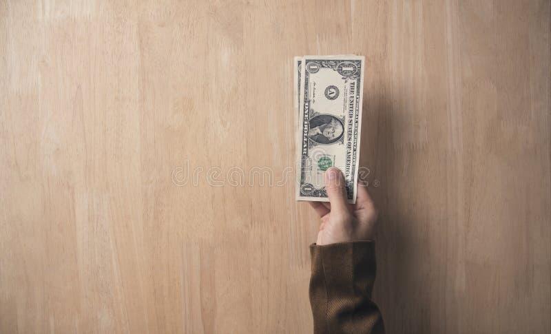 Mano del hombre de negocios que lleva a cabo el dólar en la tabla de madera en oficina fotos de archivo
