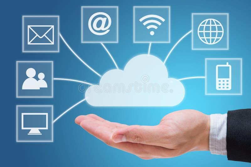 Mano del hombre de negocios que lleva a cabo la red de computación de la nube aislada en fondo azul imágenes de archivo libres de regalías