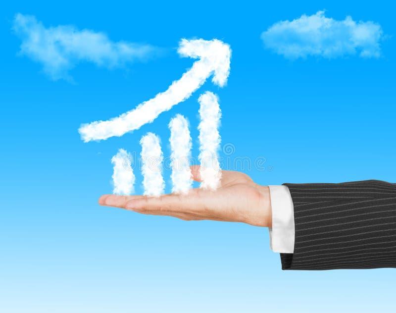 Mano del hombre de negocios que lleva a cabo un gráfico del crecimiento (hecho por la nube) en th fotografía de archivo libre de regalías