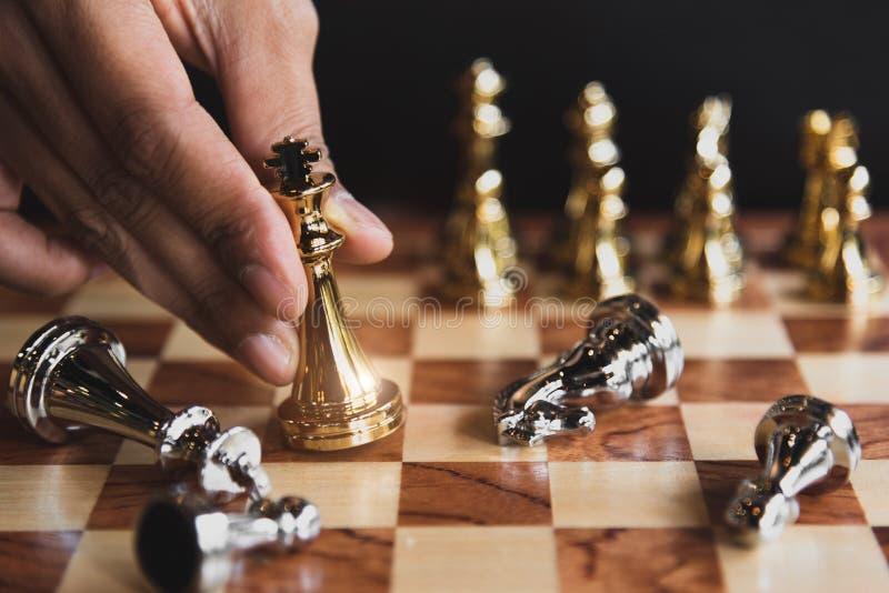 Mano del hombre de negocios que mueve la figura de oro del ajedrez para eliminar en la competencia de la batalla con el juego de  fotografía de archivo